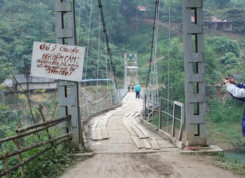 Vết nứt kéo dài từ đỉnh núi xuống bờ sông, bẻ cong chiếc cầu treo khiến người dân hoang mang, lo lắng. Ảnh: N.K