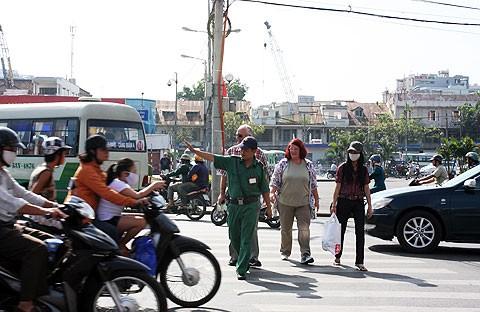 Anh Trần Duy Phong (Dội bảo vệ du khách nước ngoài) đang dẫn khách qua đường. Ảnh: Tá Lâm.