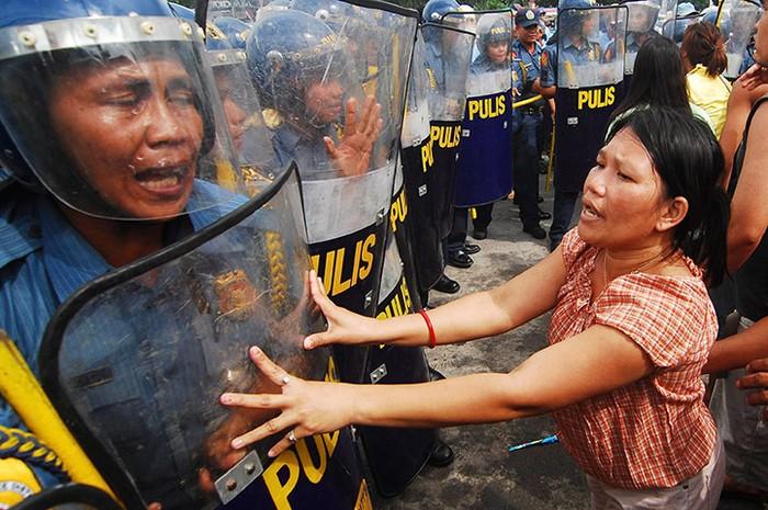 Những người định cư bất hợp pháp xung đột với cảnh sát tại đại lộ Commonwealth ở thành phố Quezon, Philippines. Hơn 1000 gia định sống trên khu đất bì giải tỏa để xây dựng một trung tâm thương mại mới