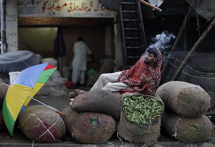 Một người bán rau nghỉ hút thuốc ở Islamabad, Pakistan
