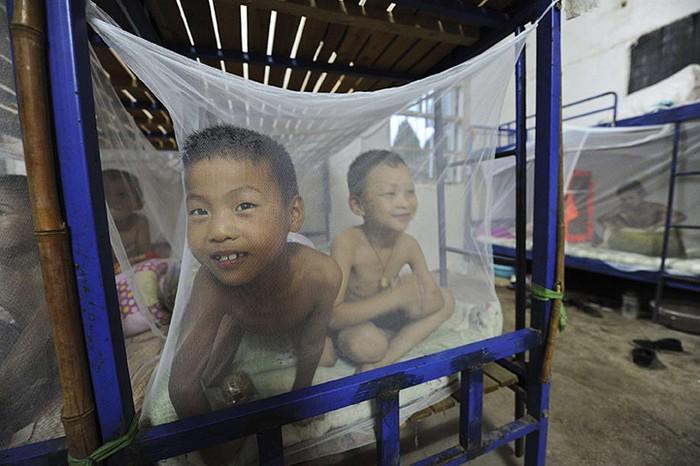 Học sinh trên giường được che màn chống muỗi tại ký túc xá của trường Tiểu học Yangguang, Trung Quốc