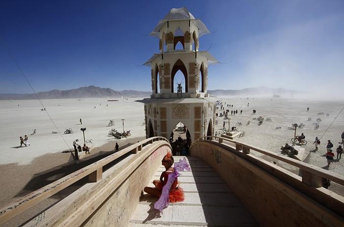 Người tham dự Lễ hội Burning Man ở Nevada (Mỹ) nghỉ ngơi sau khi ghi một thông điệp cá nhân trên tường của ngôi đền Transition