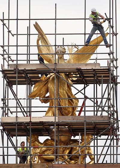 Các công nhân đang dựng giàn giáo xung quanh tượng thần Chiến thắng trên đỉnh đài tưởng niệm Nữ hoàng Victoria ở London, Anh. Đài tưởng niệm này đang trong thời gian tu sửa