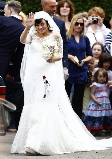 Ca sĩ - nhạc sĩ nổi tiếng người Anh Lily Allen diện váy cưới của nhà thiết kế Dephine Manivet. Chiếc váy được thiết kế rộng do cô đã mang bầu trước khi kết hôn.