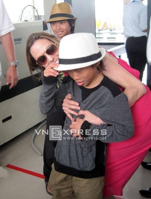Angelina Jolie ôm cậu con nuôi người Việt Pax Thiên khi cùng các con rời sân bay Côn Đảo hôm 16/11. Ảnh: Đức Mạnh.