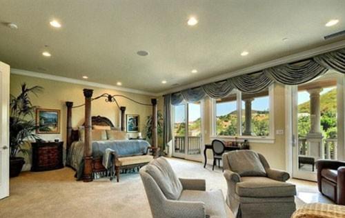 Phòng ngủ chính với cửa sổ lớn hướng ra ngoài ngọn đồi rộng lớn.